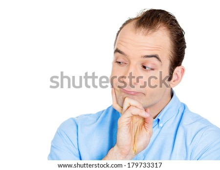 Closeup portrait of unhappy, sorry guy, sad, thoughtful young business man thinking, daydreaming deeply, bothered by mistakes, hand on chin looking away, isolated white background. Negative emotions