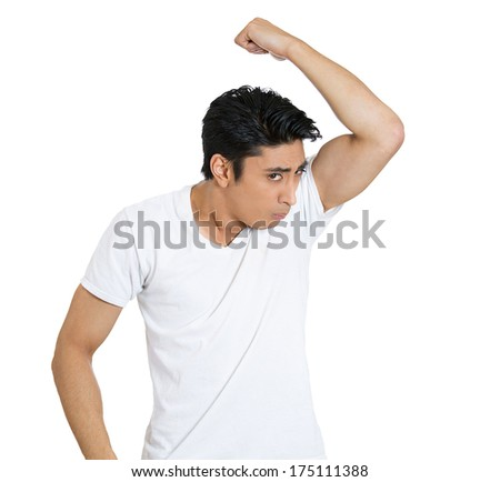 Closeup portrait of unhappy young man, smelling, sniffing himself, something stinks, very bad, foul odor situation, isolated on white background. Negative human emotions, facial expressions, feelings - stock photo