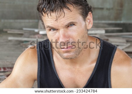 Closeup portrait of unshaven sweaty Caucasian man in black tank top working in construction area