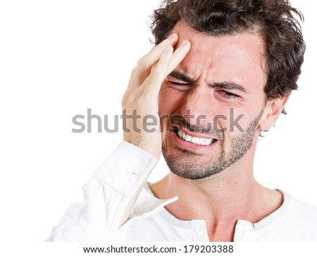 Closeup portrait of upset, stressed out young sick, tired man, handsome sad student having headache, bad day at work, school, isolated on white background. Negative human emotions, facial expressions - stock photo