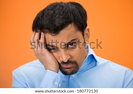 Closeup portrait of very sad, depressed, stressed, alone, defeated disappointed, gloomy young man resting his face on hand isolated orange, red background. Human emotions, facial expressions, reaction
