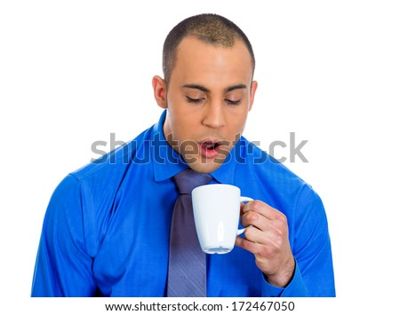 Closeup portrait of very tired falling asleep young man holding cup of coffee struggling not to crash and stay awake, keeping his eyes opened, isolated on a white background. Negative emotion feelings - stock photo