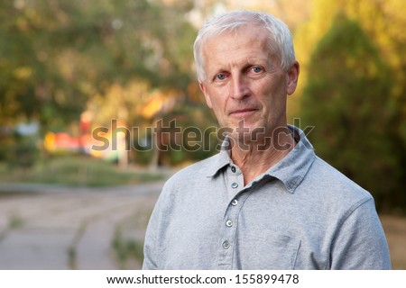 Closeup portrait of white haired and blue eyed adult man in the park outdoors - stock photo