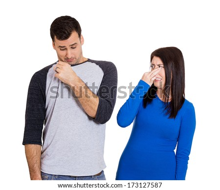 Closeup portrait of woman closing her nose, something stinks, very bad smell, odor. Guy sniffs himself. Isolated on white background. Negative emotion facial expression feeling. Unpleasant situation