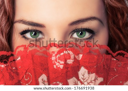 Closeup portrait of woman eyes and face hide with red fan. Secret woman - stock photo