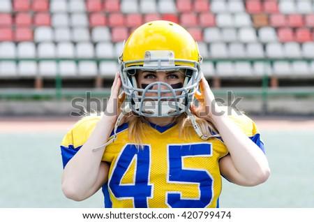 Closeup portrait of woman in american football helmet - stock photo