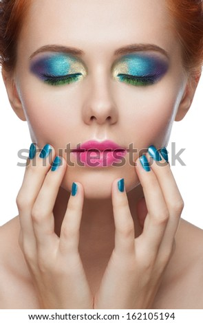 Closeup portrait of woman with colorful peacock style makeup and turquoise manicure touching her face. Bright eye makeup, closed eyes