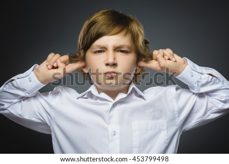 Closeup portrait of worried boy covering her ears, observing. Hear nothing. Human emotions, facial expressions - stock photo