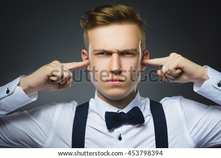 Closeup portrait of worried boy covering his ears, observing. Hear nothing. Human emotions, facial expressions - stock photo