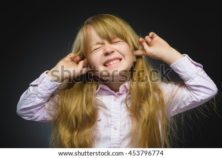 Closeup portrait of worried girl covering her ears, observing. Hear nothing. Human emotions, facial expressions - stock photo