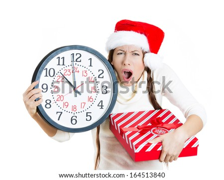 Closeup portrait of worried, stressed young woman wearing red santa claus hat, holding clock and a gift box, isolated on white background. Emotion, facial expression. Last minute christmas shopping - stock photo