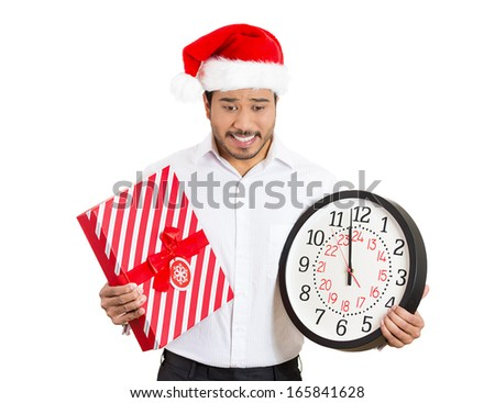 Closeup portrait of worried young man wearing red santa claus hat, holding clock and gift in hands, isolated on white background. Negative emotion facial expression. Last minute christmas shopping - stock photo