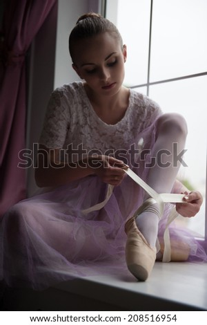 Closeup portrait of young and beautiful modern style ballet dancer sitting on window sill, tying up ballet shoes - stock photo