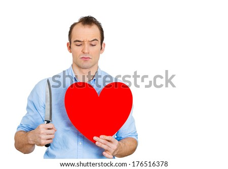 Closeup portrait of young angry man, desperate mad, cold blooded guy, looking crazy, holding heart, knife in hands, isolated on white background. Relationship, divorce, separation, broken love concept - stock photo