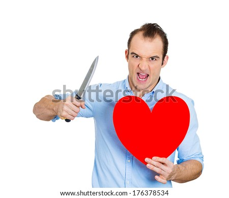 Closeup portrait of young angry man, desperate mad guy, looking crazy, screaming, holding heart and knife in hands, isolated on white background. Relationship, divorce, separation, broken love concept - stock photo