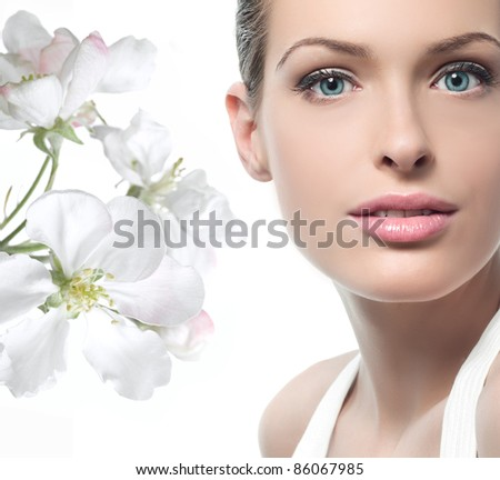 closeup portrait of young attractive caucasian woman  looking at camera with spring flowers - stock photo