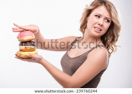 Closeup portrait of young attractive woman rejecting doughnuts isolated on white background, diet concept - stock photo