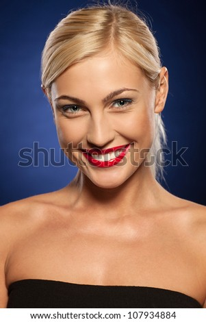 Closeup portrait of young beautiful blond female with red lips make-up smiling over blue background - stock photo