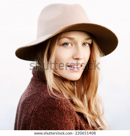 Closeup portrait of young beautiful blonde girl with blue eyes. Wearing hat and jacket. Looking at camera. Outside - stock photo