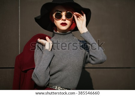 Closeup portrait of young beautiful fashionable woman with sunglasses. Lady posing on dark grey background. Model wearing stylish wide-brimmed hat. Girl looking at camera. Female fashion.Toned  - stock photo