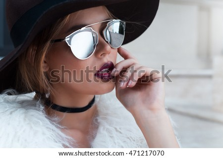 Closeup portrait of young beautiful fashionable woman with sunglasses. Lady posing on dark grey background. Model wearing stylish wide-brimmed hat, jacket. Girl looking at camera. Female fashion.Toned