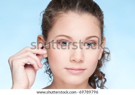 Closeup portrait of young beautiful girl with perfect skin and curly hair. Eye zone shadow make up by brush