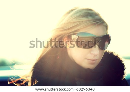 closeup portrait of young beautiful girl with sunglasses bathing in sunlight like movie star. low contrast - stock photo