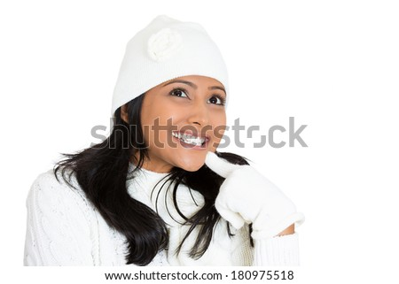 Closeup portrait of young beautiful happy pretty woman wearing winter gear attire sweater, gloves, hat, daydreaming, thinking isolated on white background. Positive emotion facial expression feelings. - stock photo
