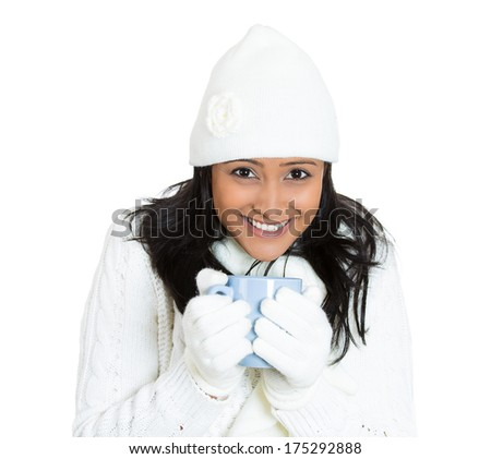 Closeup portrait of young beautiful pretty woman wearing winter gear attire sweater holding blue cup with beverage inside, isolated on white background. Positive emotion facial expression feelings. - stock photo