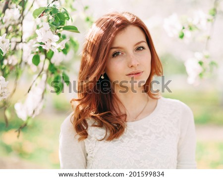 Closeup portrait of young beautiful redhead woman with an apple tree branch - stock photo