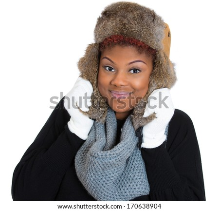 Closeup portrait of young beautiful smiling woman wearing winter gear, gray scarf, white gloves, fur ski cap, and black sweater, isolated on white background. Positive emotion facial expression - stock photo