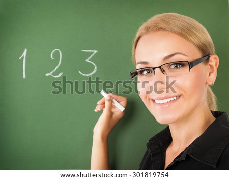 Closeup portrait of young beautiful teacher wearing glasses writing numbers on green chalkboard, start of education season, back to school - stock photo