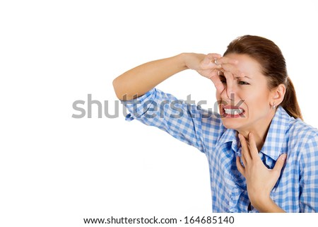Closeup portrait of young beautiful, unhappy woman covers her nose, looks away, something stinks, very bad smell, situation, isolated on white background space to left Human facial expression, emotion - stock photo