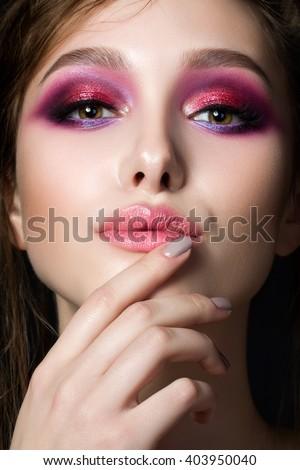 Closeup portrait of young beautiful woman with bright pink smokey eyes. Girl touching her lips. Fashion makeup. Studio shot. Modern summer make up - stock photo