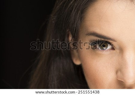 closeup portrait of young beautiful woman with natural makeup over black background