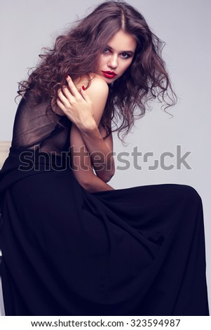 Closeup portrait of young beautyful woman with curly hair. Sitting and posing in studio. Bright makeup.