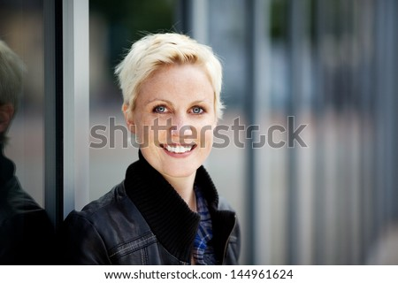 Closeup portrait of young blond woman smiling - stock photo