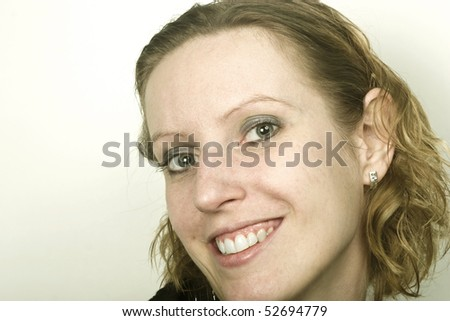 Closeup portrait of young blond woman, smiling and looking at camera. lots of workspace on left side. - stock photo