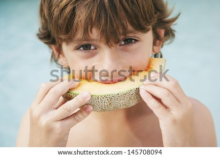 Closeup portrait of young boy eating slice of melon