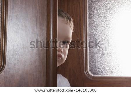 Closeup portrait of young boy peeking while standing behind wooden door - stock photo