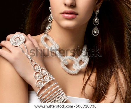 Closeup portrait of young brunette woman with vintage silver diamond pendant earrings and chain jewelry necklace on black background