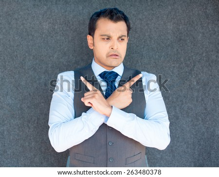 Closeup portrait of young business man thinking, daydreaming, pointing opposite directions, looking confused, isolated gray background. Negative emotion facial expression. Short-term memory loss - stock photo