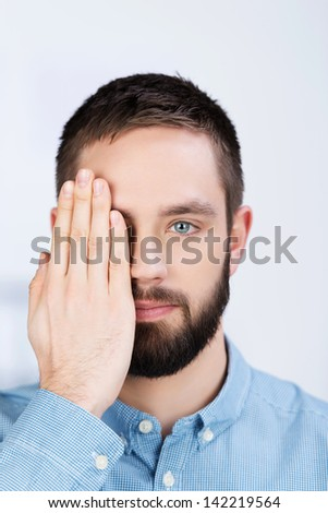 Closeup portrait of young businessman covering his one eye with hand in office - stock photo