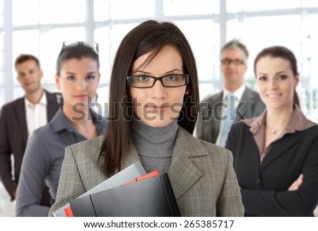 Closeup portrait of young businesswoman and team standing at office.