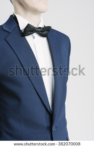 Closeup Portrait of Young Caucasian Man in Blue Suite and Bow Tie. Vertical Shot - stock photo