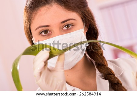 closeup portrait of young female biologist wearing mask experimenting with leaf in lab - stock photo