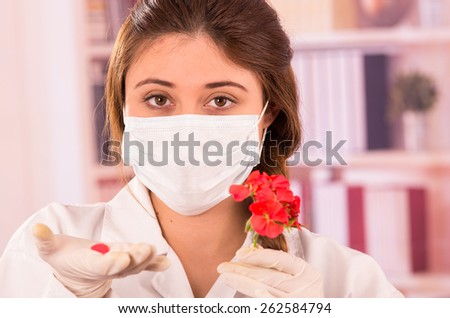 closeup portrait of young female biologist wearing mask experimenting with red flower in lab - stock photo