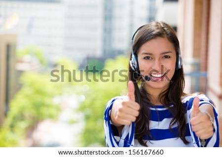 Closeup portrait of young female customer service representative, call center agent, support staff or operator with phone headset on balcony giving us thumbs up, isolated on a city background - stock photo
