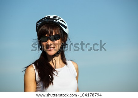 Closeup portrait of young female cyclist over sky background - stock photo