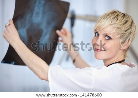 Closeup portrait of young female doctor holding hip Xray report in hospital - stock photo